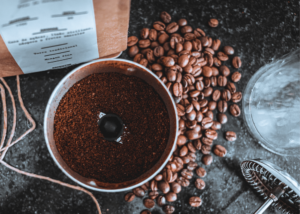 best coffee grinder for french press, photo of ground coffee with coffee beans next to it