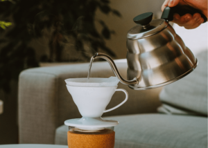 best gooseneck kettle, photo of someone using a silver gooseneck kettle to make pour over coffee in a white mug
