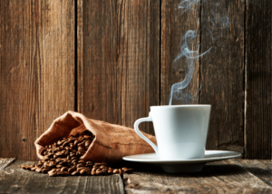 How long do roasted coffee beans last, photo of a bag of coffee beans spilling over and a hot cup of coffee in a white mug next to it with a wooden background.