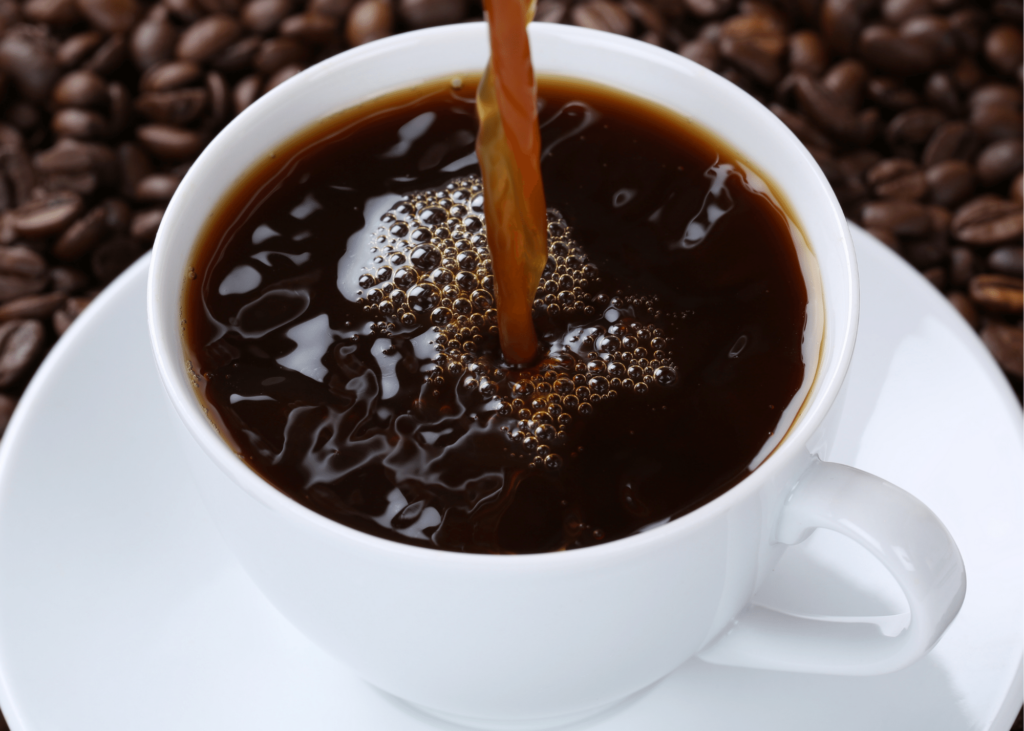 how to clean a keurig 2.0, photo of a black coffee being poured into a white mug surrounded by coffee beans