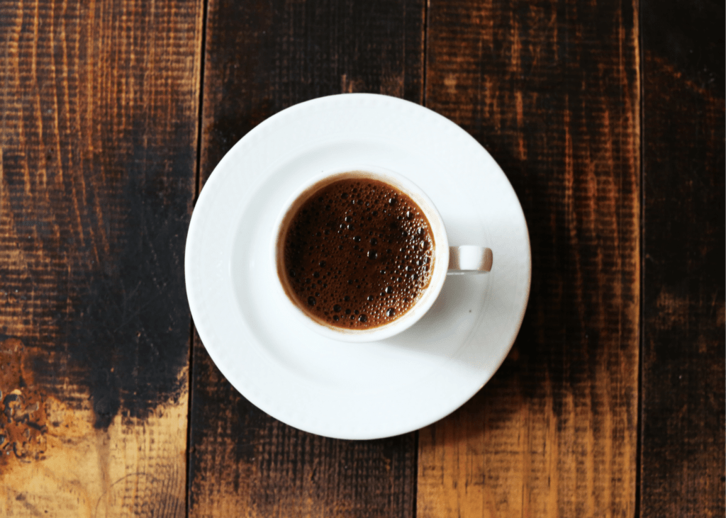 how to make an americano, photo of a white coffee mug with coffee on a wooden surface