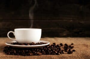 Best Coffee Maker with Grinder, photo of a white coffee mug sitting on whole coffee beans