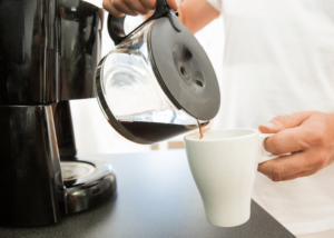best 4 cup coffee maker, photo of a person pouring coffee from the pot into a white mug