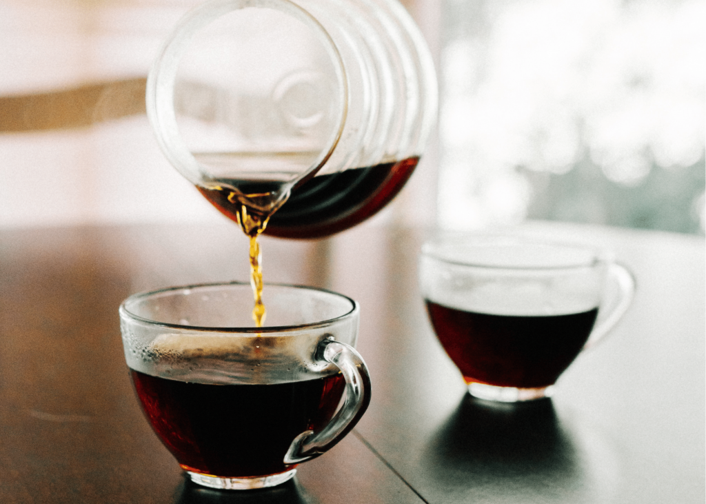 how to make low acid coffee, photo of two clear glass coffee mugs sitting on a table and a clear coffee pot pouring coffee into one.