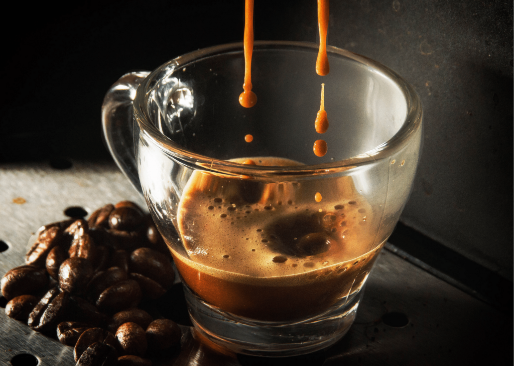 espresso dripping into a clear mug, coffee beans sitting next to the mug and a dark background. Article keyword: delonghi magnifica