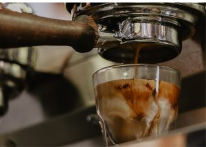 breville infuser, photo of a shot of espresso pouring into a clear little glass