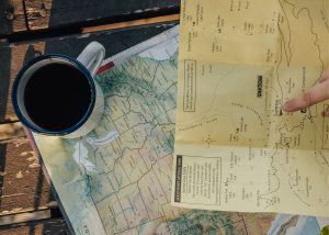 makita coffee maker, photo of black coffee sitting on top of two maps on a wooden table